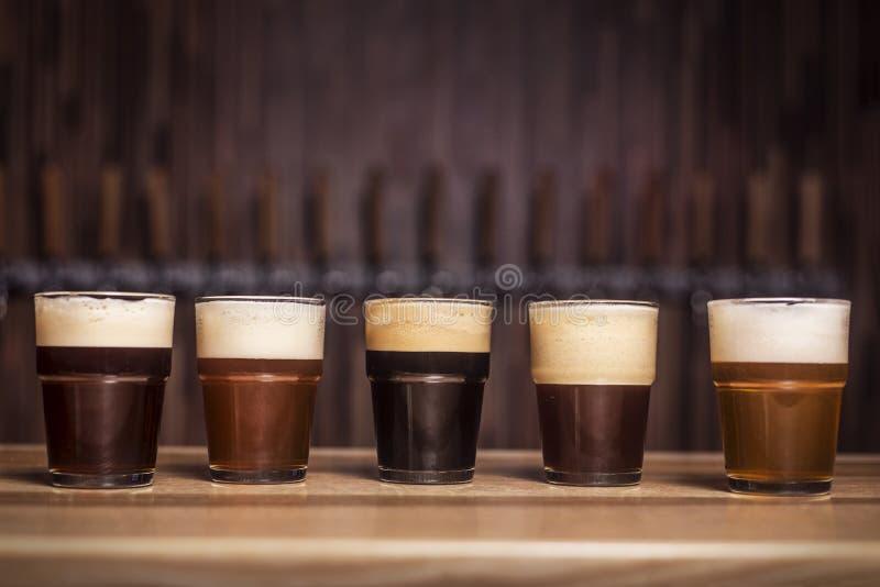 Flera olika öl står i rad arkivfoton