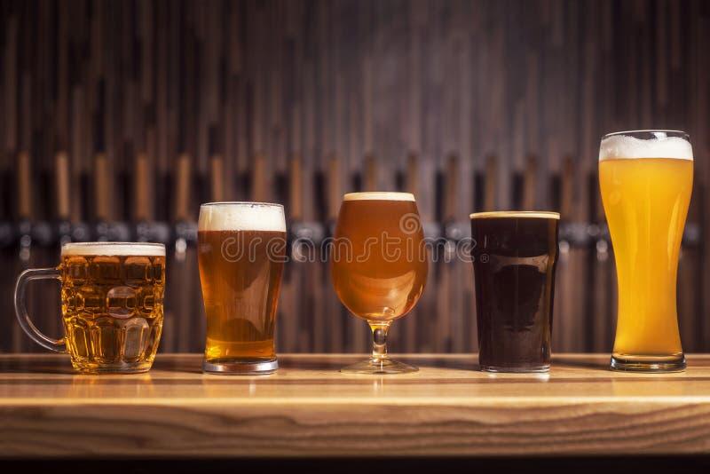 Flera olika öl står i rad på stången arkivfoton