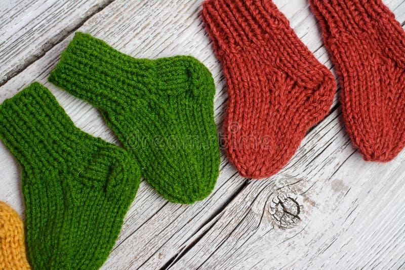 Flera par av små woolen sockor för nyfött på trätappningtabellen arkivbild