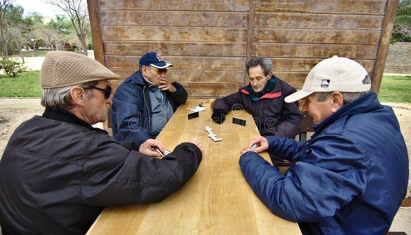 Flera pensionärer spelar den utomhus- leken av dominobrickor på en tabell i royaltyfri fotografi