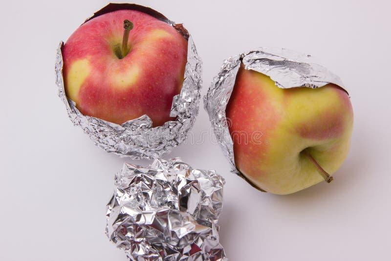 Flera röda och gula mogna äpplen som slås in i folie på en vit b fotografering för bildbyråer