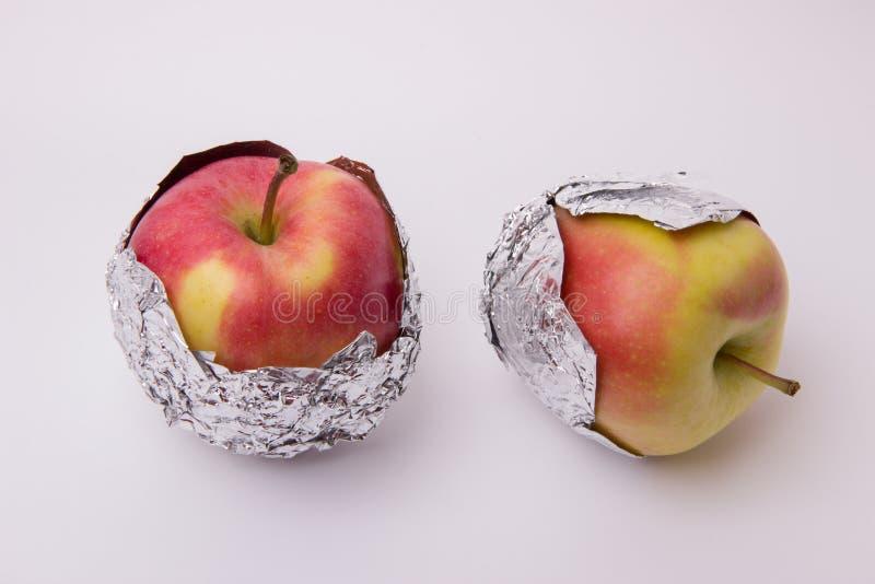 Flera röda och gula mogna äpplen som slås in i folie på en vit b royaltyfria bilder