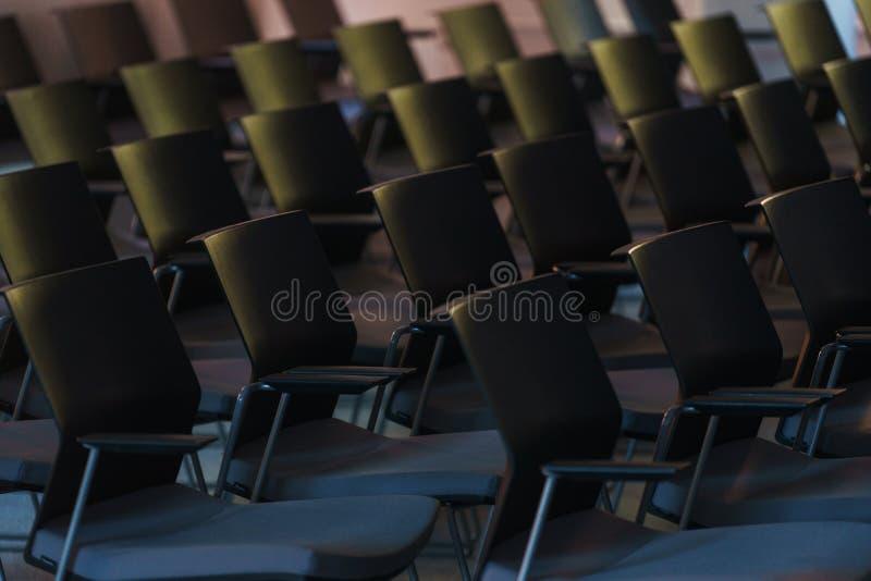 Flera rader av tomma plast- stolar i åhörarna som är förberedda för anförandet för högtalare` s framme av studenter eller journal royaltyfri bild