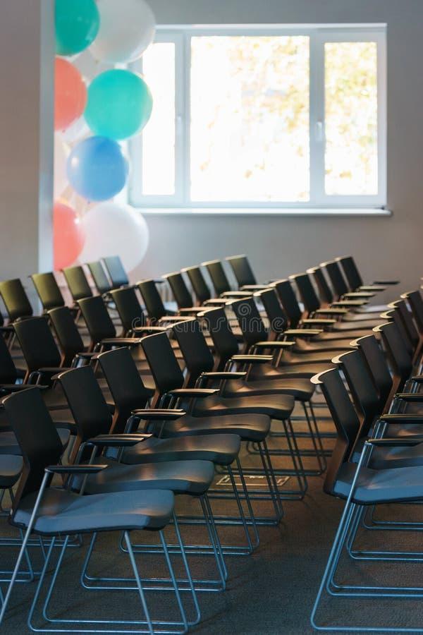 Flera rader av tomma plast- stolar i åhörarna som är förberedda för anförandet för högtalare` s framme av studenter eller journal fotografering för bildbyråer