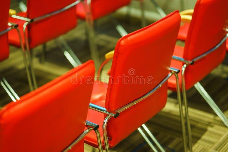 Flera rader av tomma stolar i ?h?rarna som f?rbereds f?r h?gtalarens anf?randeframdelen av studenter eller journalister och ?sk?d arkivfoton