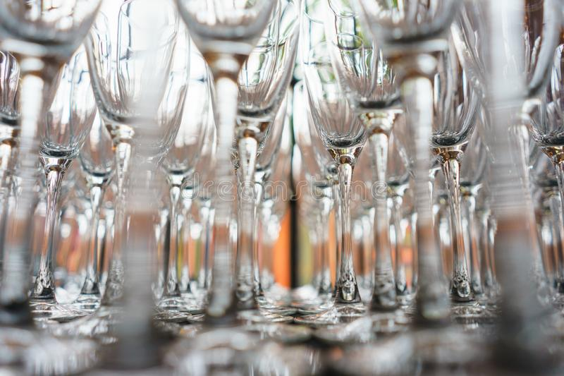 Flera rader gör klar genomskinliga rena exponeringsglas för vin och champagne på räknaren som förbereds för drinkar arkivbild