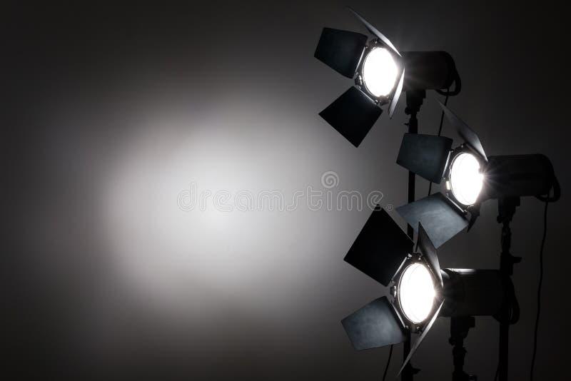 Flera reflektorer på den svarta bakgrunden i fotostudio royaltyfria foton