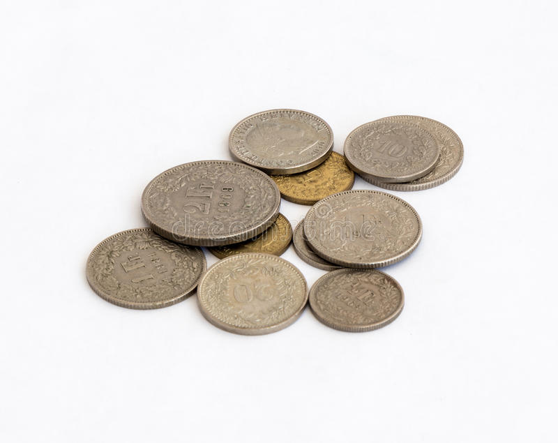 Flera schweiziska mynt av olikt värde som isoleras på en vit bakgrund arkivfoton