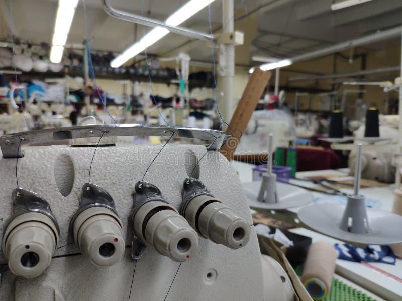 Flera trådspänningsregulatorer på ett symaskinslut upp på en suddig bakgrund av en systuga arkivfoton
