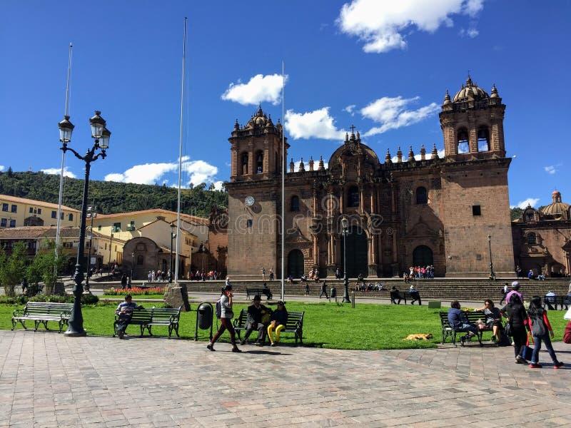 Flera turister beundrar sikten av Plaza de Armas i härliga och forntida Cusco, Peru arkivbild