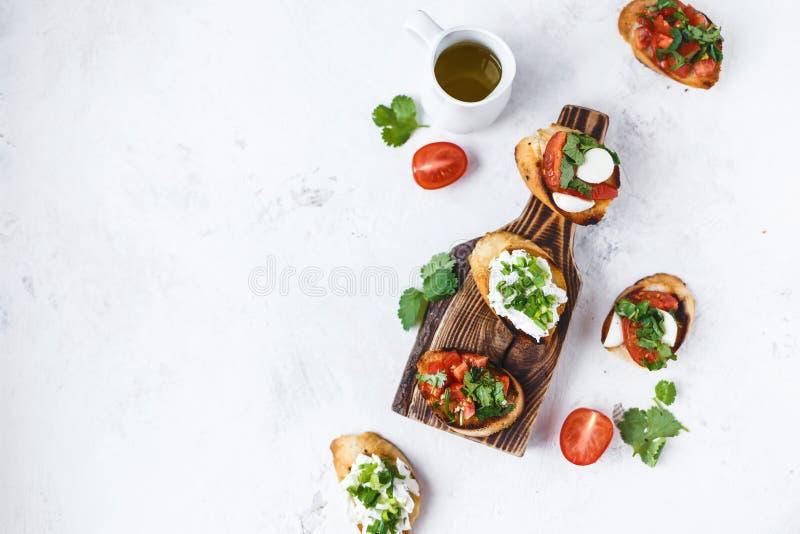 Flera typer av den italienska bruschettaen med tomater, mozzarellaen och örter på ett träbräde på en ljus bakgrund royaltyfri bild