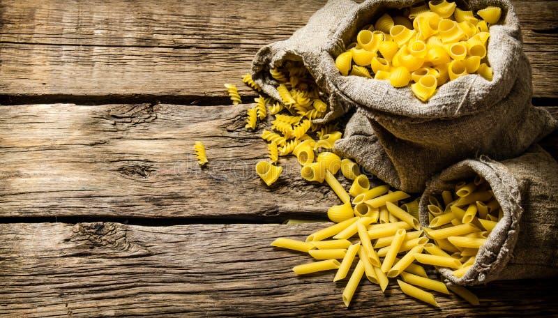 Flera typer av pasta i gamla påsar arkivbild