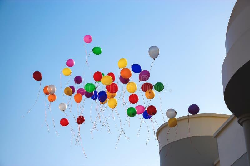 Flerfärgade ballonger flyger den högt klara near skolan för blå himmel kopiera avstånd fotografering för bildbyråer
