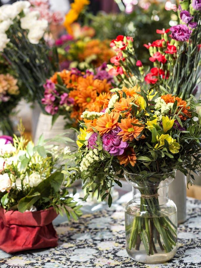 Flerfärgade buketter av blommor i olika behållare arkivfoton