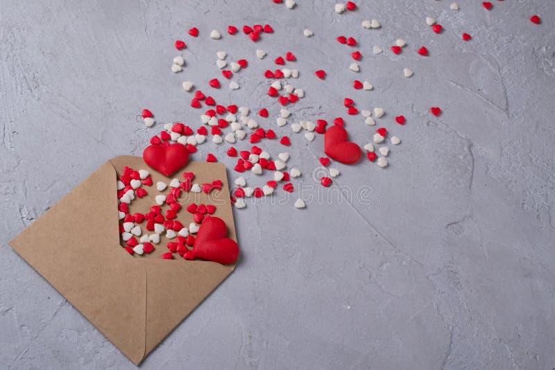 Flerfärgade hjärtor för sötsaksockergodis flyger ut ur post- kuvert för hantverkpapper Lyckligt begrepp för dag för valentin` s fotografering för bildbyråer