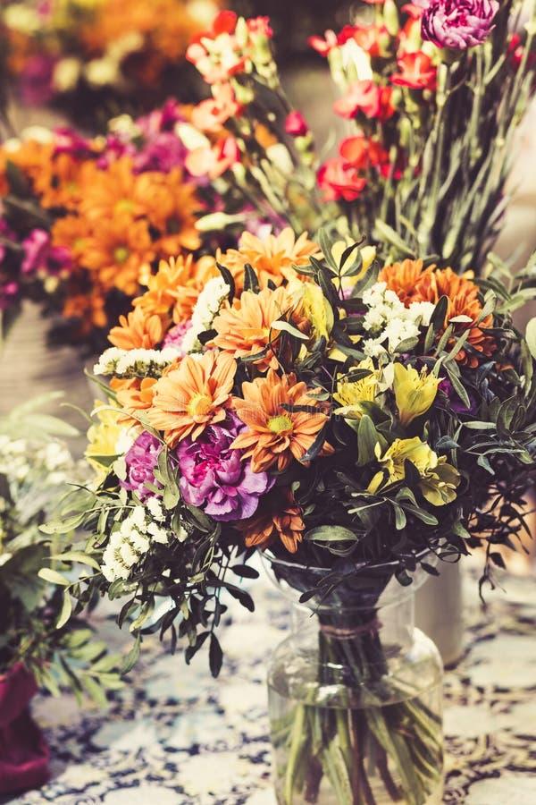 Flerfärgade vårblommor i exponeringsglasvas arkivfoto