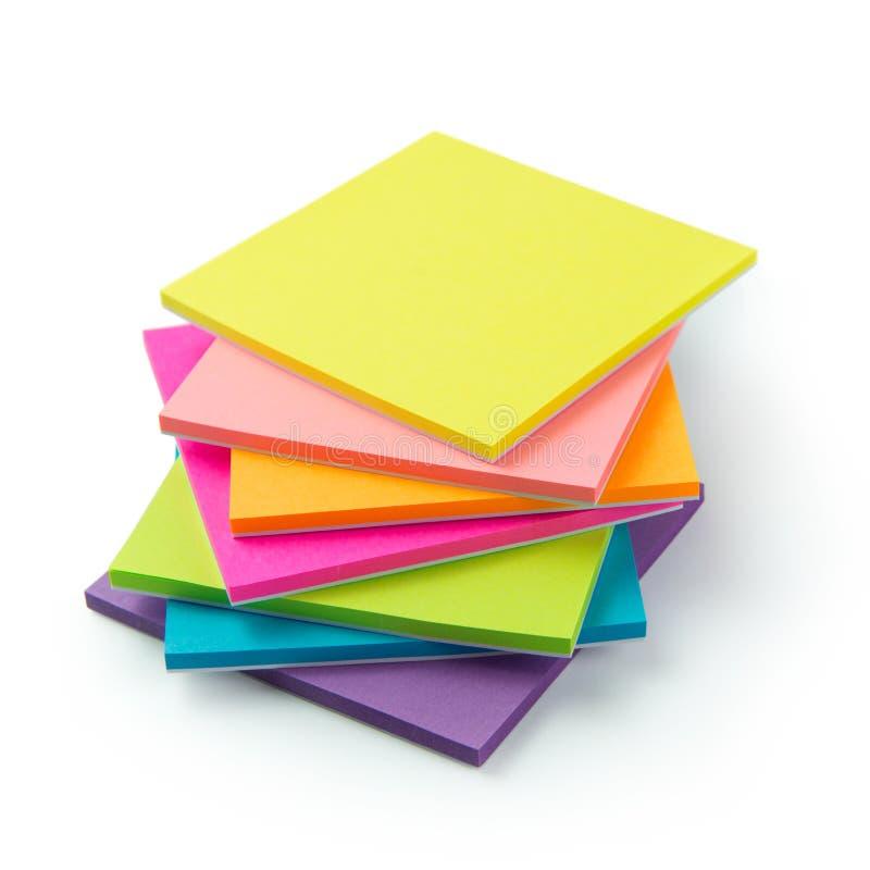 Flerfärgat stolpe-honom klibbiga anteckningsböcker royaltyfria bilder