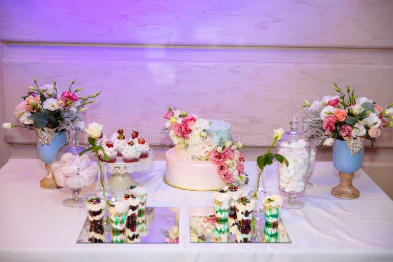 Flernivå-bröllopstårta- och godisstång, en tabell med sötsaker och efterrätter på tabellen Buffé med läckra muffin royaltyfri bild