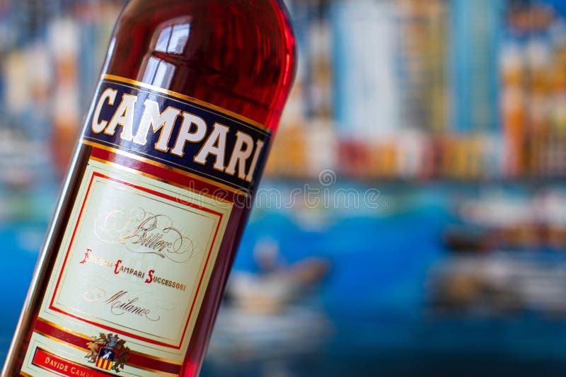 Fles Campari met achtergrond van cityscape, een alcoholische likeur die die kruiden en fruit bevatten, in 1860 in Novara, Italië  stock afbeeldingen