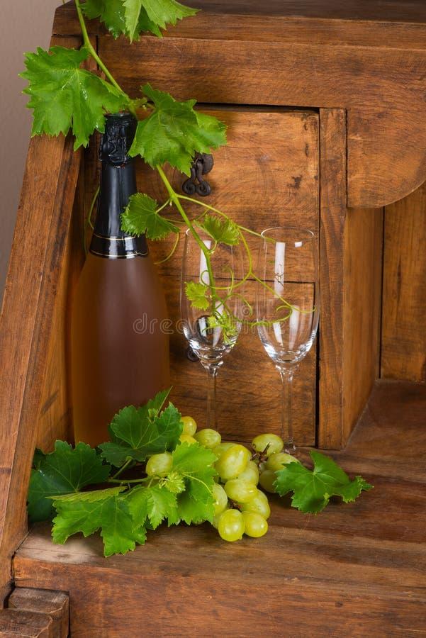 Fles champagne, druif en twee glazen stock foto's
