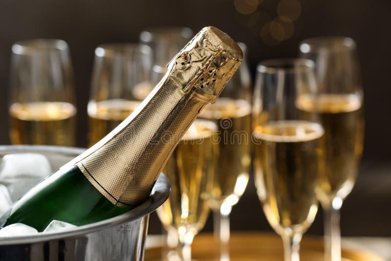 Fles champagne in emmer met ijs en glazen op vage achtergrond stock foto's