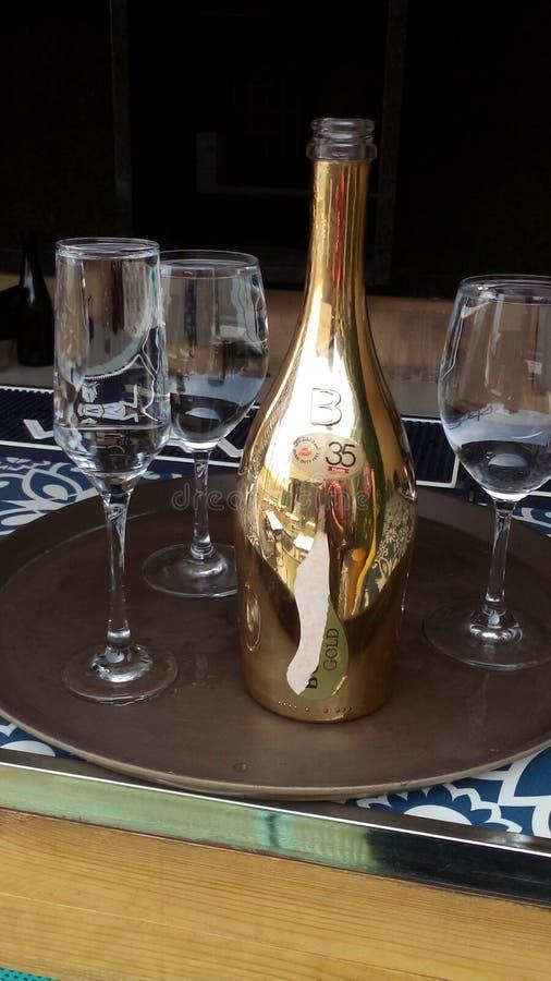 Fles champagne met glazen die water op het hebben stock afbeeldingen