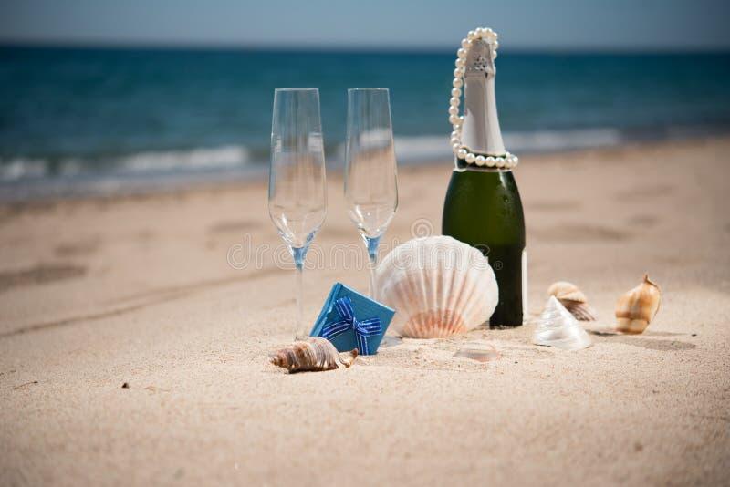 Fles champagne op het zandige strand met een giftdozen en zij royalty-vrije stock afbeelding