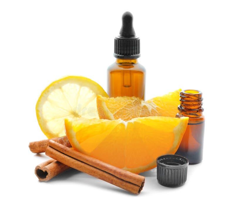 Fles citrusvruchtenetherische olie, pijpjes kaneel en vruchten op witte achtergrond royalty-vrije stock afbeeldingen