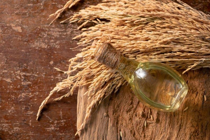 Fles de olie van rijstzemelen en unmilled rijst op houten achtergrond royalty-vrije stock foto's