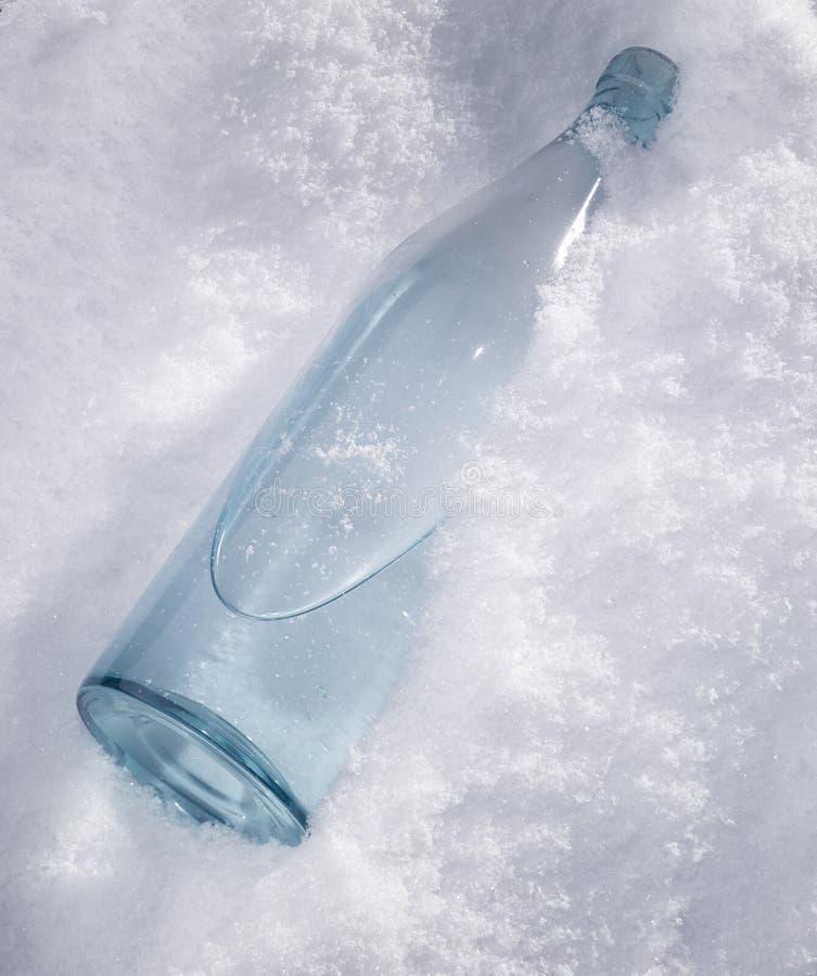 Fles in de sneeuw stock afbeeldingen