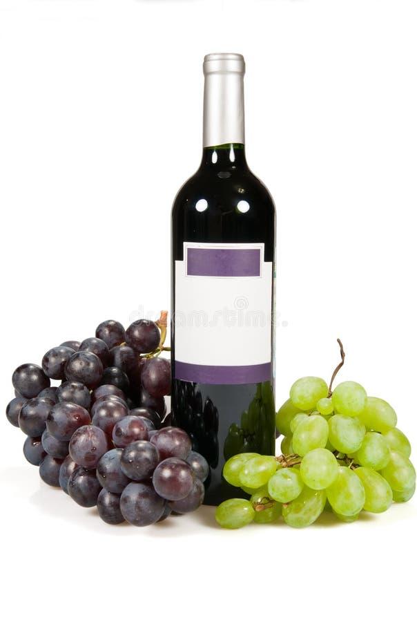 Fles en druiven van rode en groene kleur. stock foto's