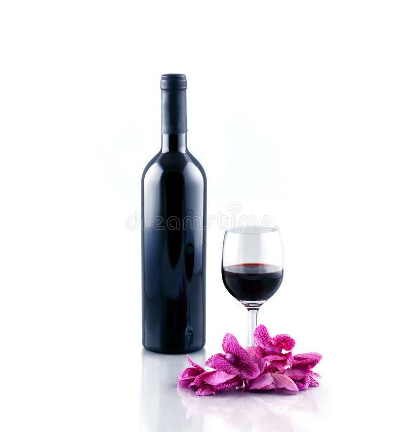 Fles en glas rode wijn die op witte achtergrond wordt geïsoleerd stock afbeeldingen