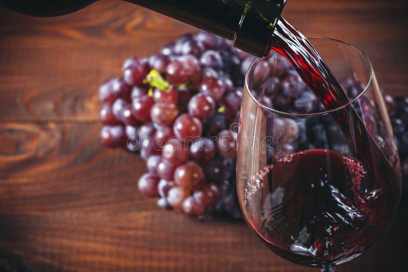Fles en glas rode wijn, druif en cork stock afbeelding