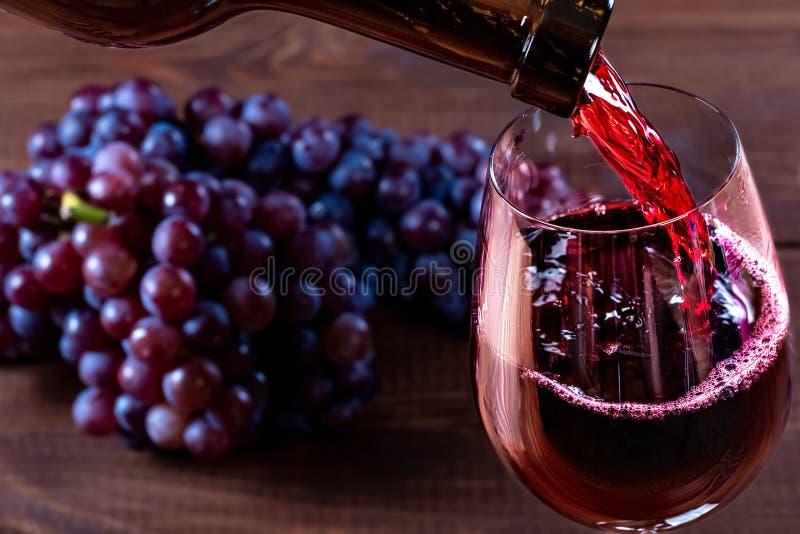Fles en glas rode wijn, druif en cork op houten achtergrond stock foto
