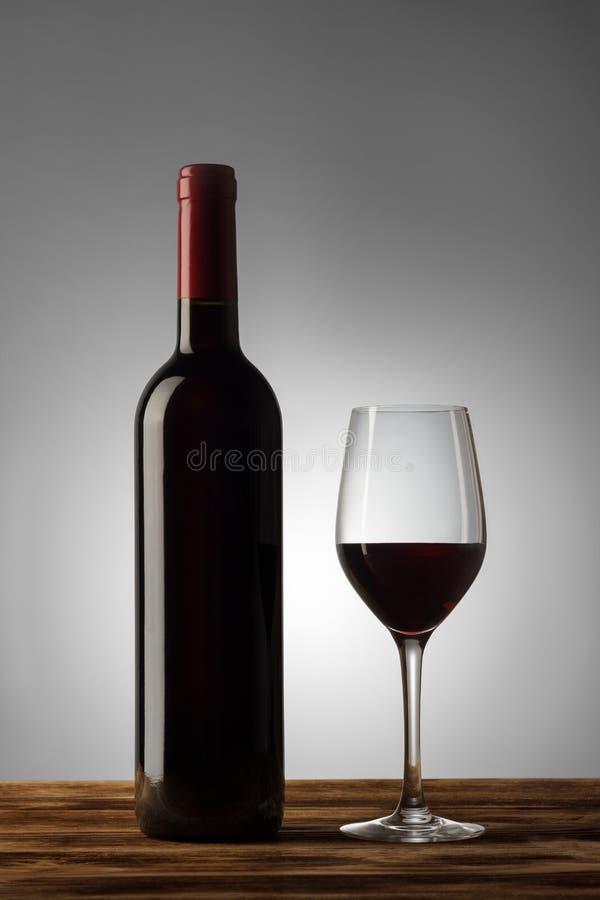 Fles en glas rode wijn met een lichte gradiënt op de achtergrond royalty-vrije stock fotografie