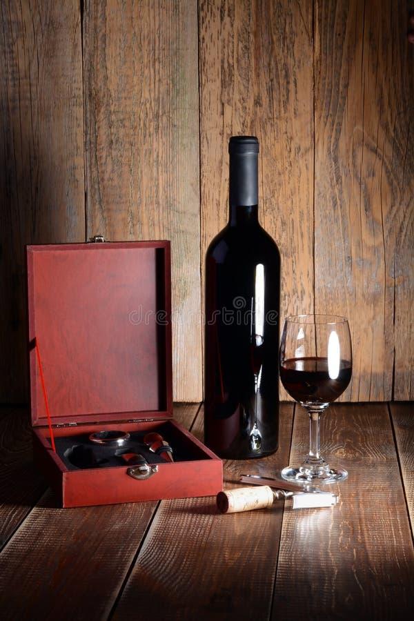 Fles en glas rode wijn op houten lijst stock fotografie