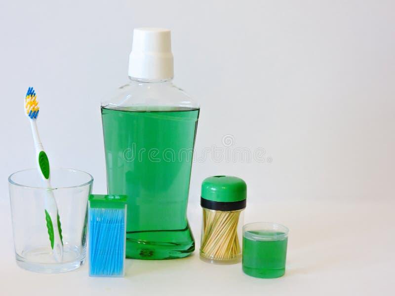 Fles en glas van mondspoeling op badplank met tandenborstel Tand mondeling hygiëneconcept Reeks mondelinge zorgproducten royalty-vrije stock foto's