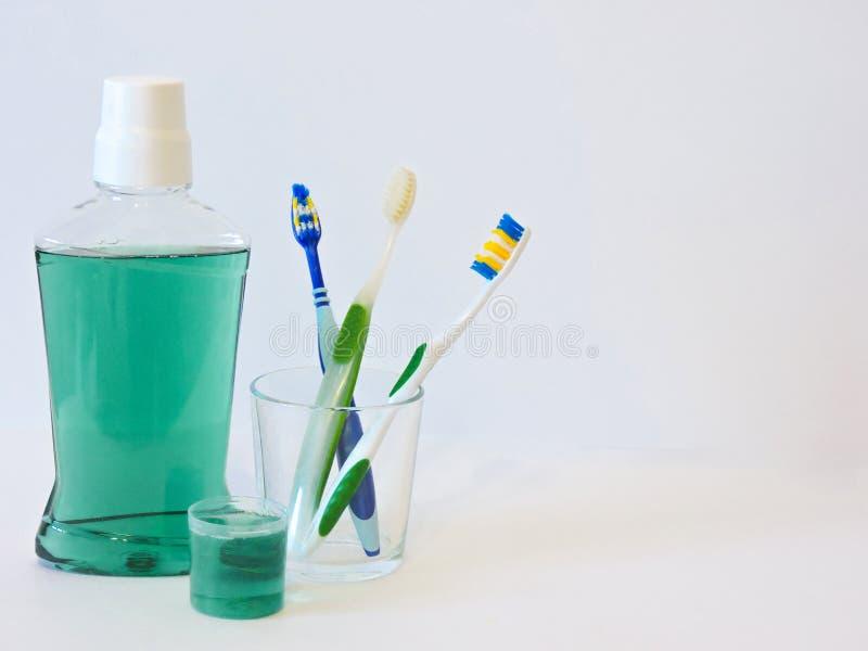 Fles en glas van mondspoeling op badplank met tandenborstel Tand mondeling hygiëneconcept Reeks mondelinge zorgproducten royalty-vrije stock afbeeldingen