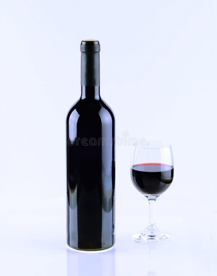 Fles en glas wijn op witte achtergrond wordt geïsoleerd die stock foto's