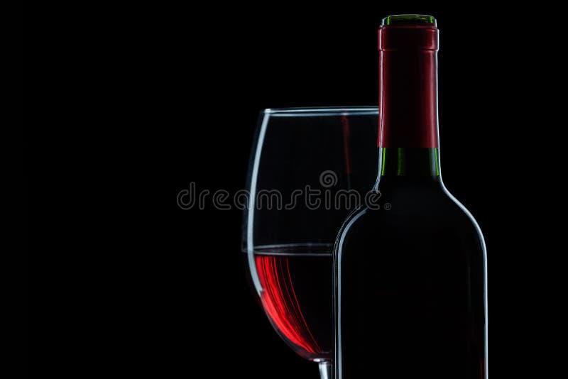 Fles en wijnglas met rode wijn op zwarte dichte omhooggaande mening als achtergrond stock afbeelding