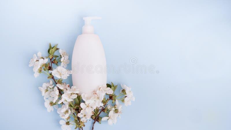 Fles en witte bloemen op blauwe achtergrond Het concept natuurlijke schoonheidsproducten De ruimte van het exemplaar stock afbeelding