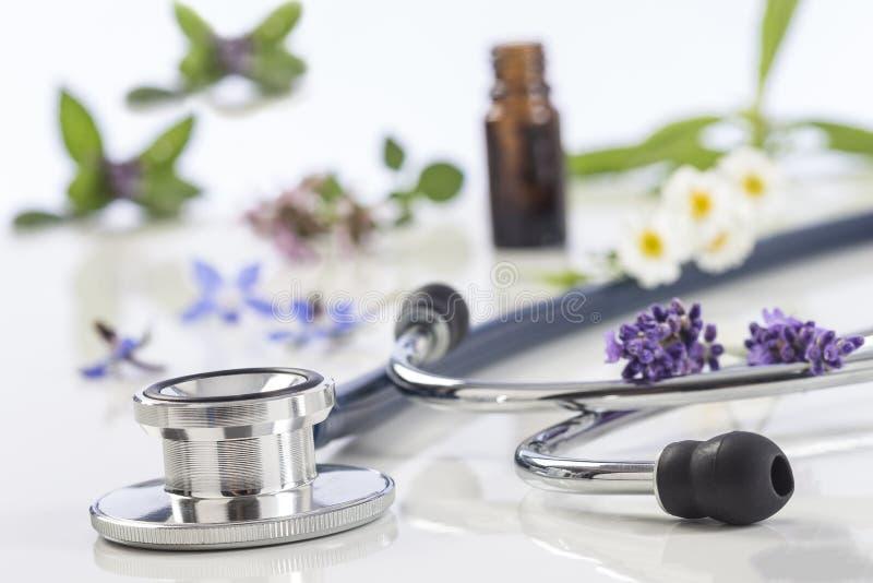 Fles etherische olie met geneeskrachtige installatie en stethoscoop royalty-vrije stock foto