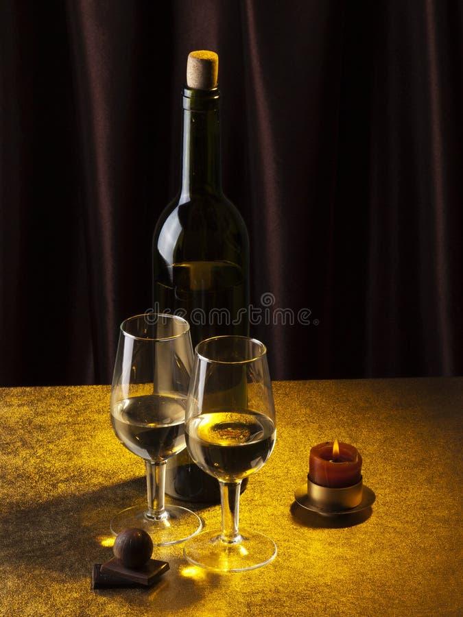 Fles, glas met wijn en kaars stock foto