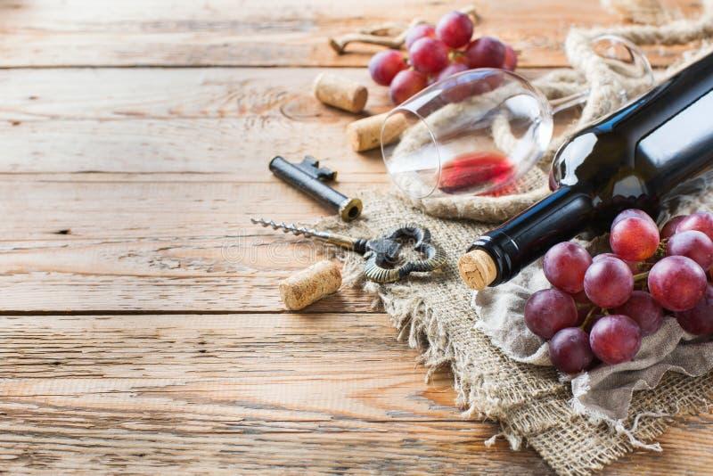 Fles, kurketrekker, glas rode wijn, druiven op een lijst stock fotografie