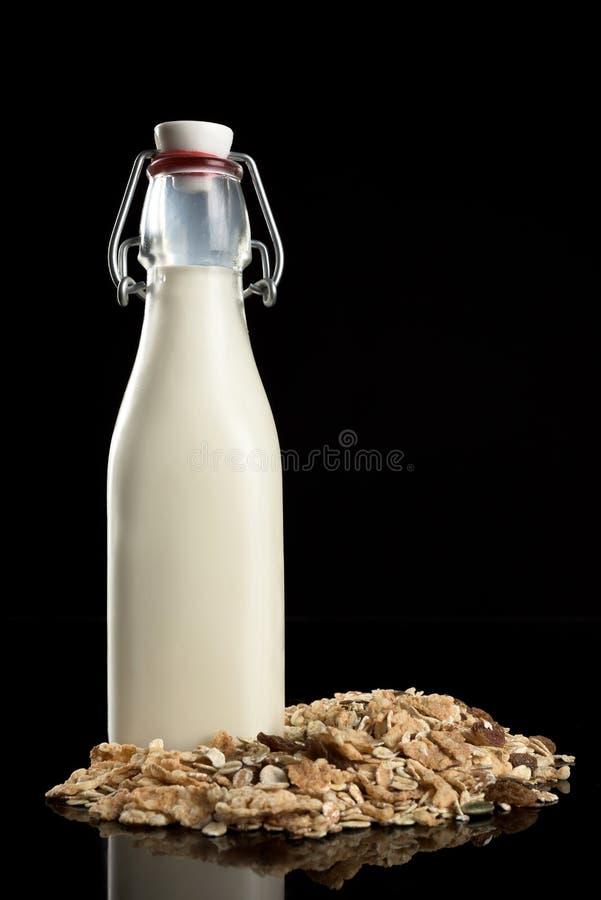 Fles melk en ontbijtgraangewassen op zwarte achtergrond stock afbeelding