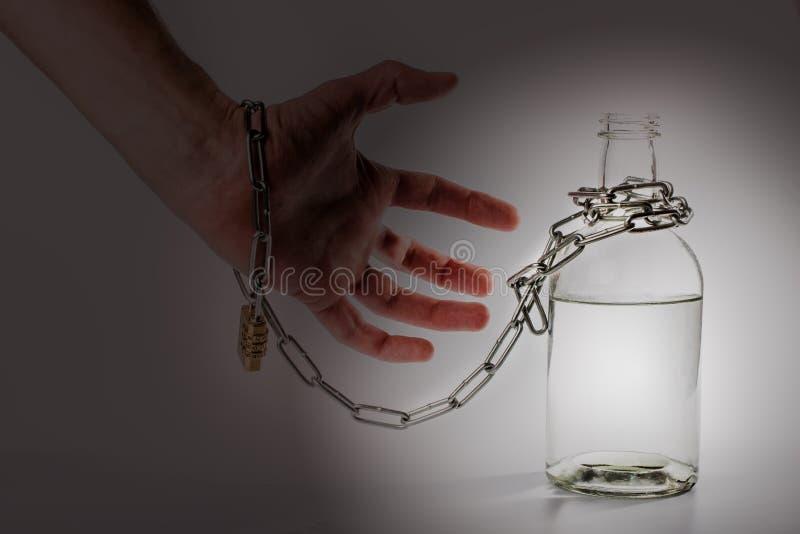 Fles met alcohol en ketting stock afbeelding
