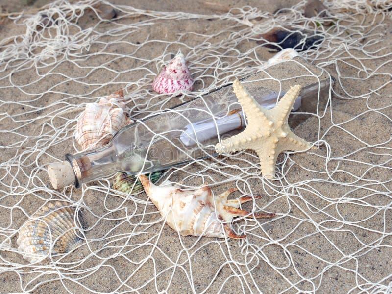 Fles met bericht in het visserijnet stock afbeelding