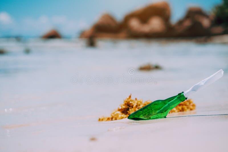 Fles met bericht op wit paradijs zandig strand met vage achtergrond Conceptuele foto stock afbeeldingen
