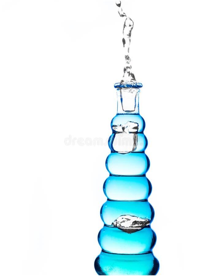 Fles met blauw water die uitgieten royalty-vrije stock afbeeldingen