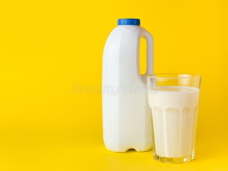 Fles met verse melk met handvat en glas melk op gele achtergrond Spot omhoog voor merkmalplaatje stock afbeeldingen